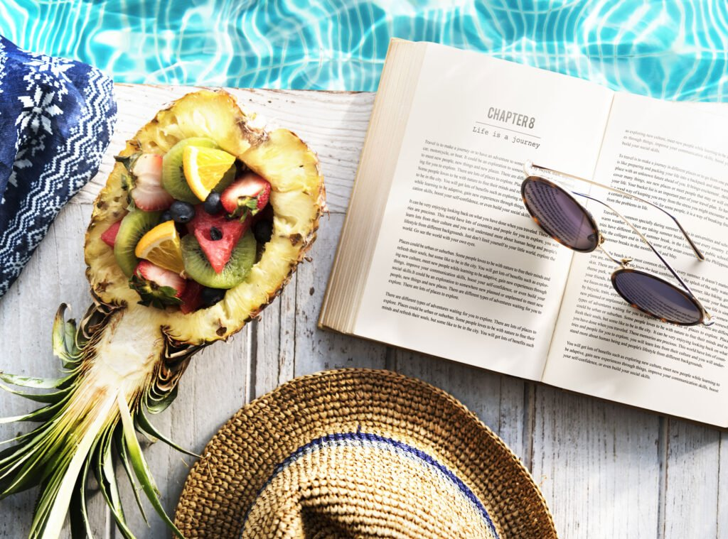 open book by the pool | How to Have a Stellar Summer Staycation